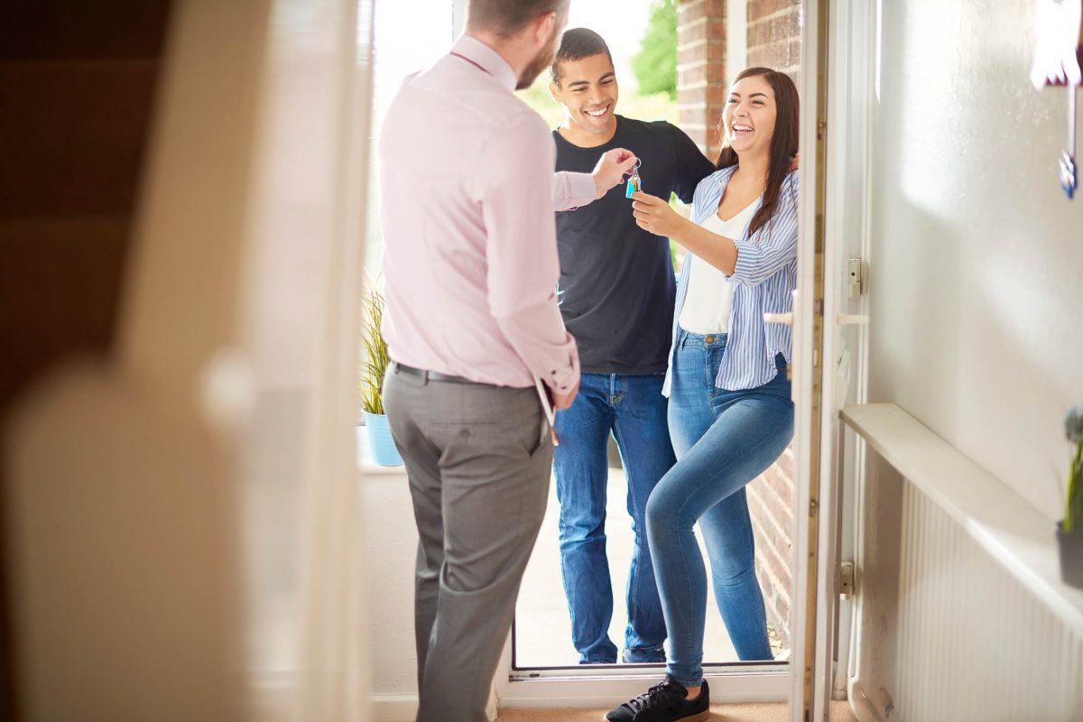 corretor entregando as chaves de uma apartamento para um casal