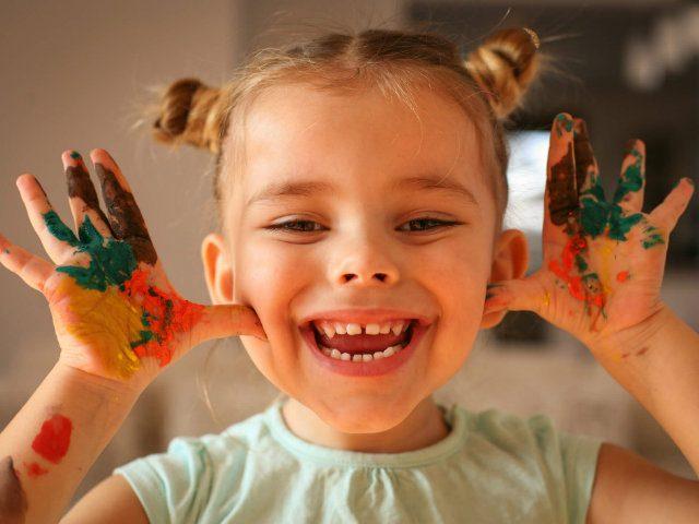 criança sorrindo com as mãos cheia de tinta